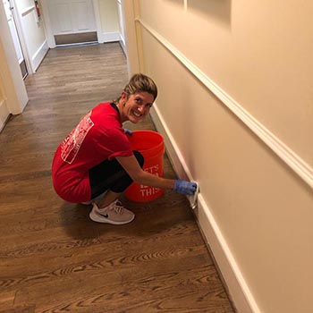 A Volunteer cleans baseboards at the Evelyn D. Reinhart Guest House